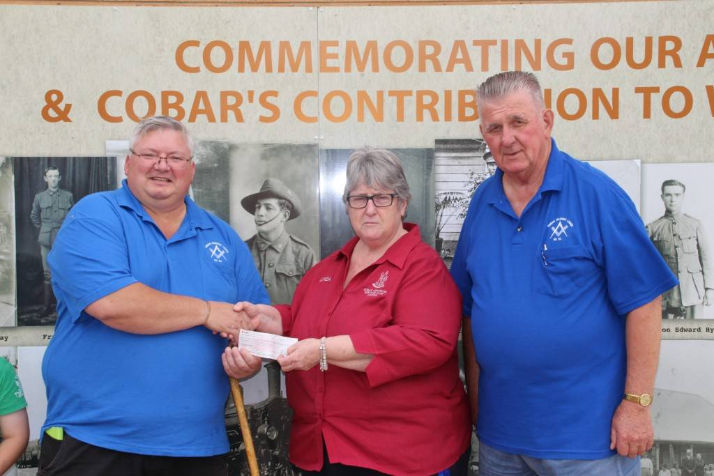 Cobar Lodge No 97 members Tony Punzet and Heinz Goldmann presented Cobar Memorial Services Club secretary/manager Linda Carter with a $1,000 donation last Friday to help fund the next stage of the club's World War II commemorative wall mural.