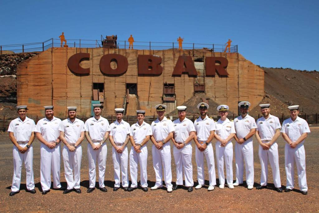 Some of the HMAS Rankin crew in front of the Cobar sign on Friday.