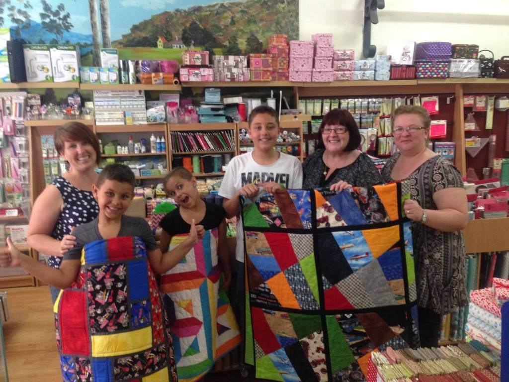 Cobar quilters Sarah Cryer, Colleen Flynn and Ana Kok (far right) are pictured with James, Claire and Alex Cremona who have been recipients of a local group's handmade quilts. ▪ Photo contributed