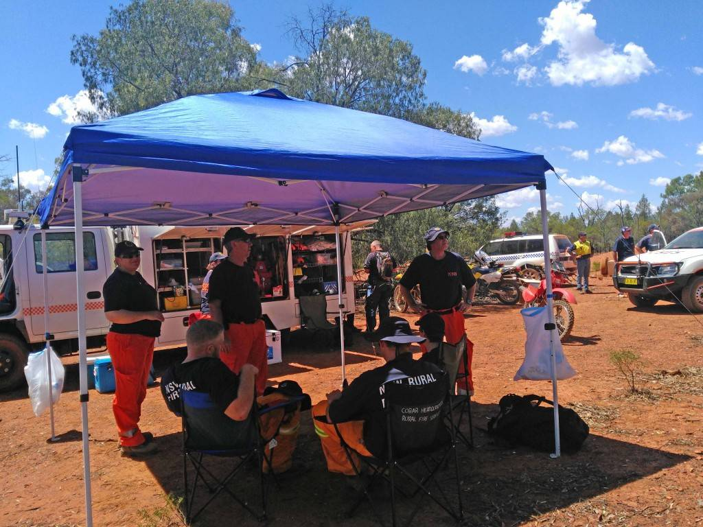 Cobar State Emergency Service and Rural Fire Service volunteers take a well earned break during the search for the missing woman near Girilambone last week. ▪ Photo contributed