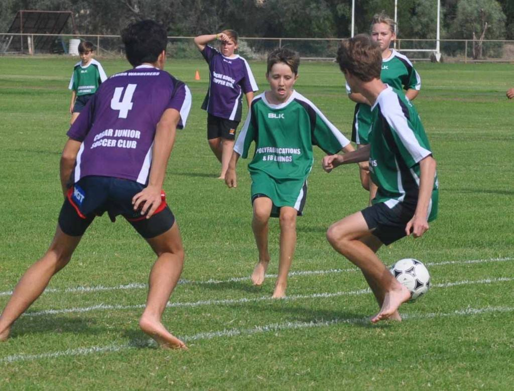 Kids played barefoot football (soccer) on Saturday at Ward Oval as part of the Cobar Junior Soccer Club's Indigenous Football Week celebrations. Pictured at centre is Chad Buckman with Johnny Best (No 4 at left) and Jakob Brown (right).