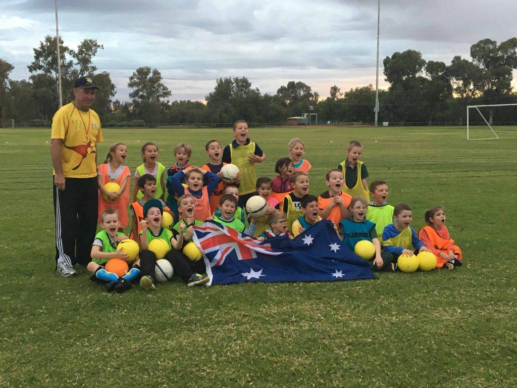Former Australian Socceroos captain Paul Wade was back in Cobar last week and did some soccer skills sessions with local junior players. He coached three sessions  Minis (5-7 years), Mids (8-11 years) and Seniors/Opens (12 years plus) putting them through a range of coaching drills and fun ball skills. The sessions were well  attended with over 100 local players taking part. Paul is pictured above with the Minis group. ▪ Photo contributed