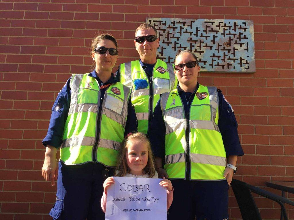Cobar paramedics Anita Hodgkinson, Shane Peate and Lara Hughes (with Livinia Cain, daughter of paramedic Rachel Cain) wore yellow vests last Wednesday in protest of the  State Government slashing their death and disability scheme. ▪ Photo contributed