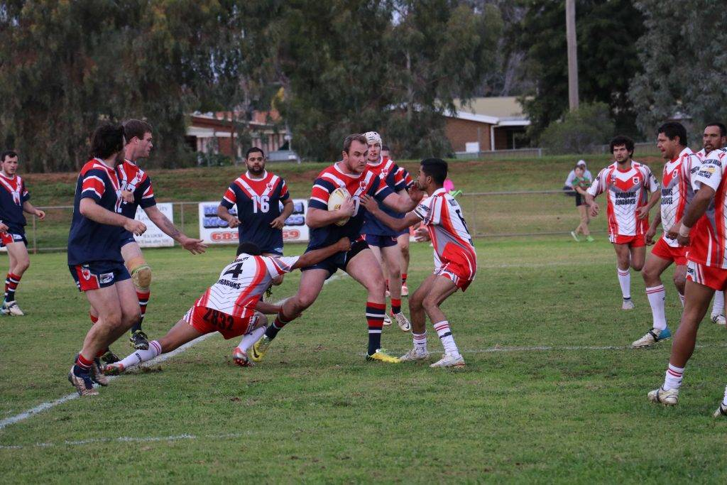 Roosters captain/coach Ben Simon forces his way through the tough Walgett defence in the Barwon Darling major semi final game on Saturday at Tom Knight Memorial Oval.